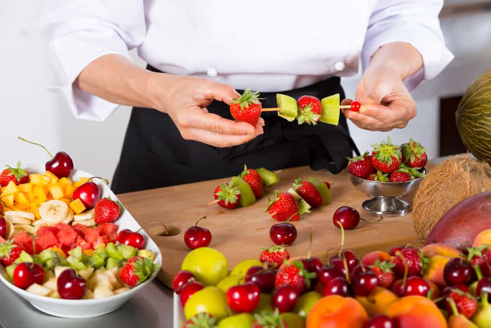 Chef preparing a variety of mixed fruit skewers