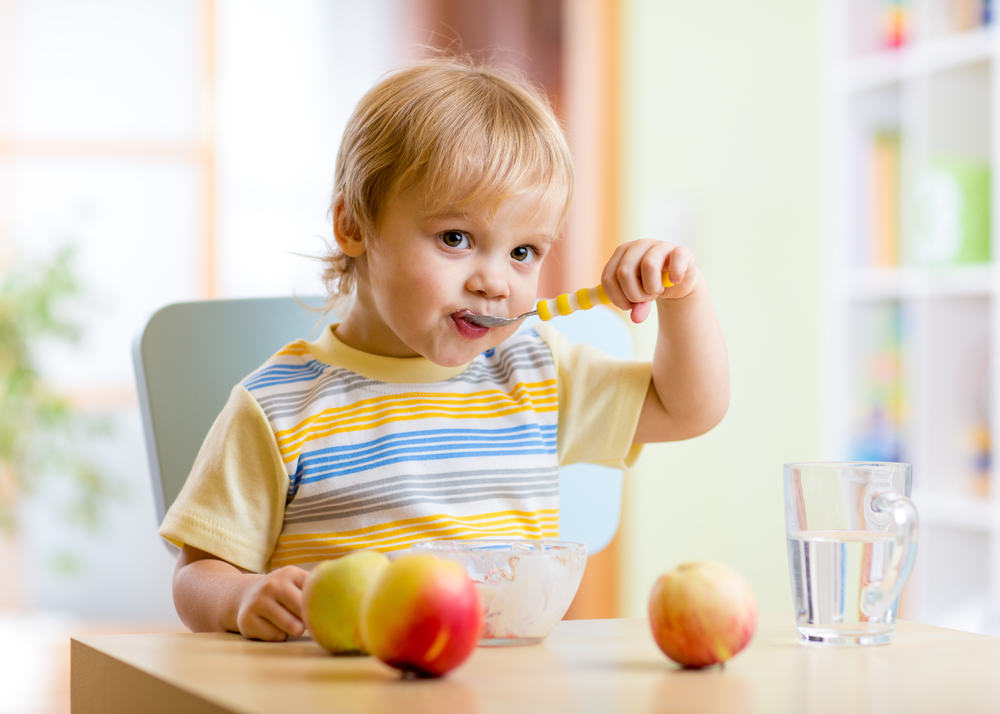Cute child eating healthy food with gusto