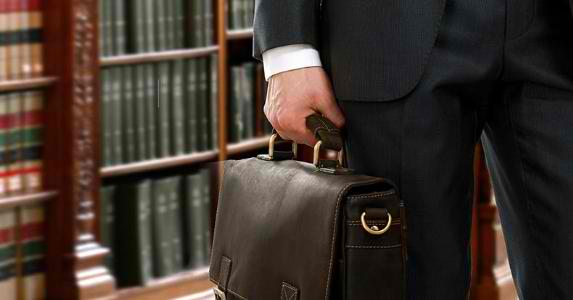lawyer-in-library-holding-briefcase-closeup_573x300